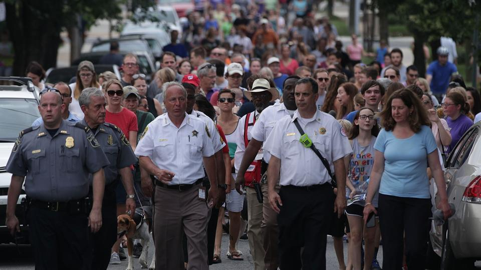 Led by local law enforcement officials, local residents march to a nearby church to show solidarity after a shooting at the Eugene Simpson Stadium Park June 14, 2017 in Alexandria, Virginia. US House Majority Whip Rep. Steve Scalise (R-LA) and multiple congressional aides were shot by a gunman during a Republican baseball practice.