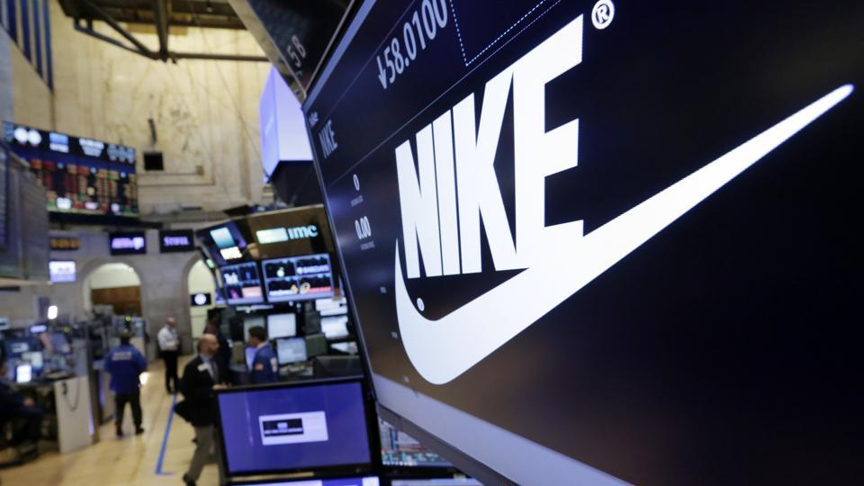 In this Wednesday, March 22, 2017, file photo, the Nike logo appears above the post where it trades on the floor of the New York Stock Exchange. On Thursday, June 15, 2017, Nike said it plans to cut about 1,400 jobs, reduce the number of sneaker styles it offers by a quarter and sell more shoes directly to customers online. The company says the changes to its business structure will help it offer more products to customers faster.