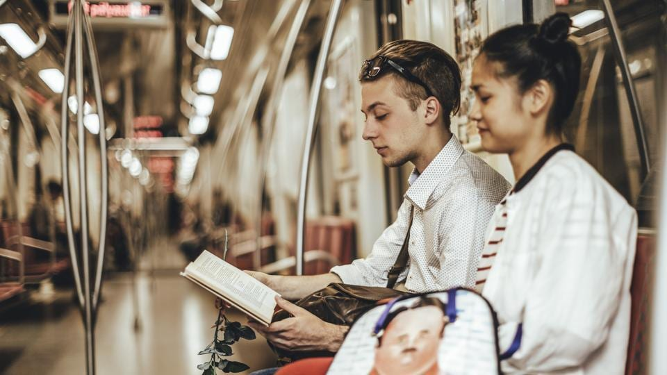 Youngsters read a book while travelling in a metro train.