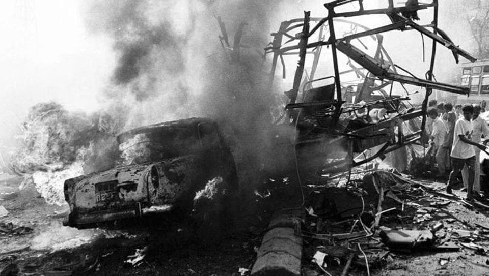 The skeletal remains of a bus seen alongside burning vehicles outside the passport office after a massive explosion in Mumbai in 1993.