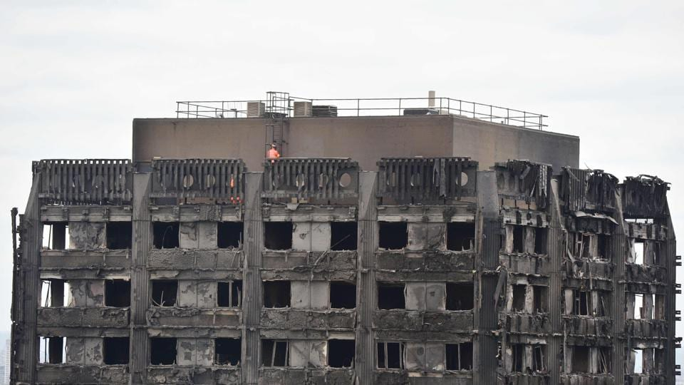Emergency workers inspect the roof of Grenfell Tower, a residential tower block in west London which was gutted by fire, on June 16, 2017. Dozens of people are feared dead in the London tower block fire as emergency workers continued searching for bodies in the high-rise on Friday, warning they may never be able to identify some of the victims.