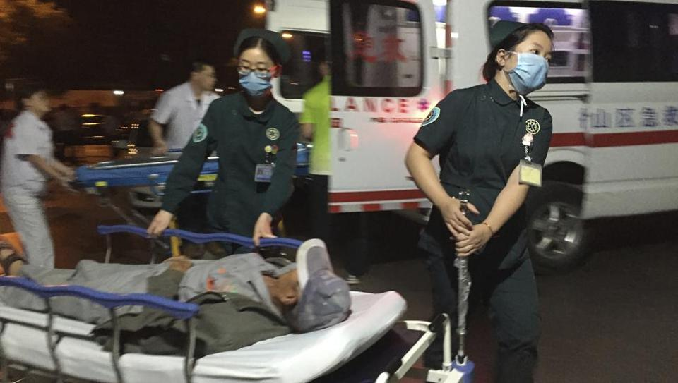 In this photo released by China's Xinhua News Agency, medical workers transport a person injured in an explosion outside a kindergarten into a hospital in Fengxian County in eastern China's Jiangsu Province early Friday, June 16, 2017.