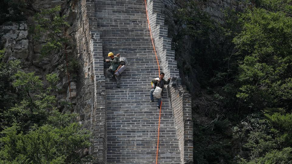 Workers carry their tools and belongings as they climb down the Great Wall. (Damir Sagolj/REUTERS)