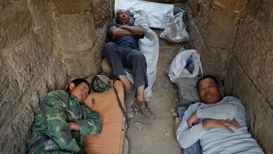People rest after working on the reconstruction of the Great Wall.  (REUTERS)