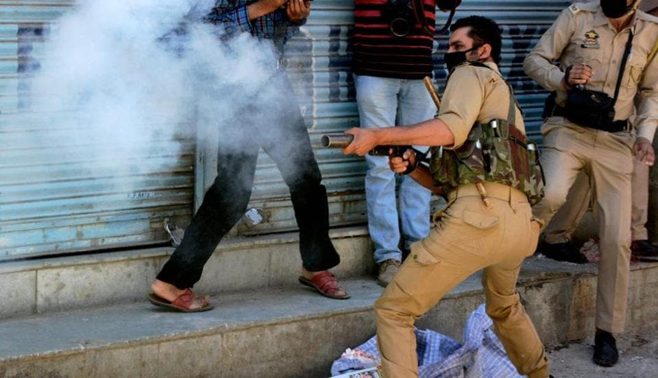 A policeman fires tear gas shells towards protesters during clashes in Srinagar.