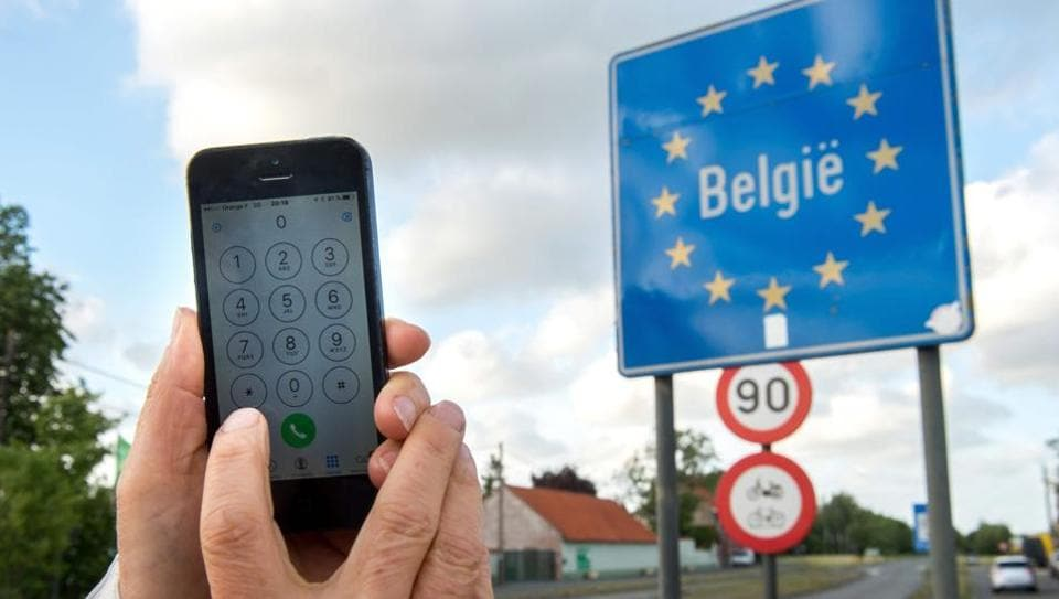 This file photo taken on June 06, 2017 shows a man using his mobile phone in Boeschepe at the Franco-Belgian border on June 6, 2017. On June 15, 2017, mobile roaming charges will be abolished in the countries of the European Union.