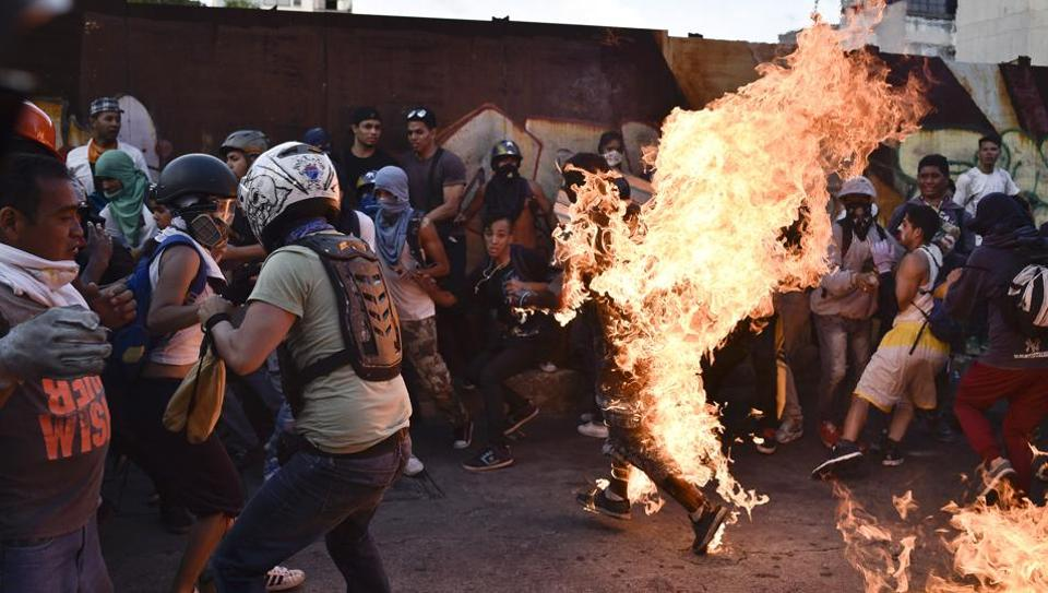 This file photo taken on May 20, 2017 shows opposition demonstrators set an alleged thief on fire during a protest against the government of President Nicolas Maduro in Caracas. It is not just Venezuela's economy and political system that are sick, experts say -- but society itself.