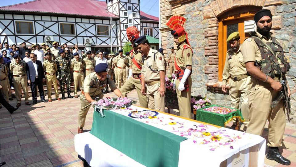 Director general of Jammu and Kashmir Police SP Vaid lays a wreath on the coffin of policeman Shahzad Dilawar Sofi at police headquarters in Srinagar,on June 16, 2017.