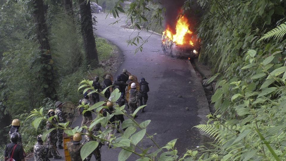 Security personnel watch from a distance as a vehicle torched by suspected protestors after a raid at GJMchief Bimal Gurung's office, goes up in flames in Darjeeling, West Bengal. (AP)