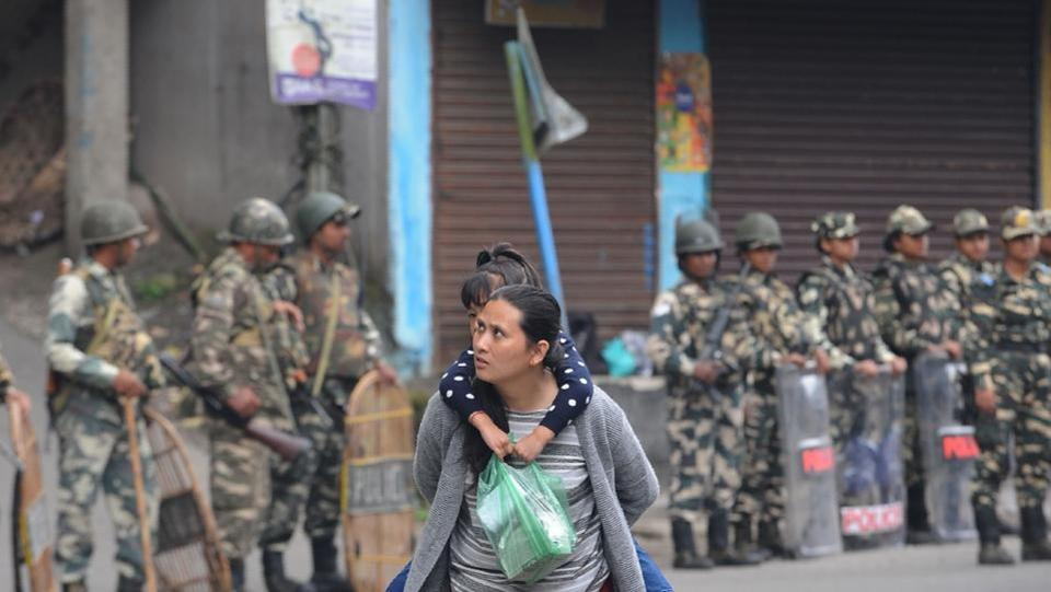 A woman carries her child as paramilitary personnel stand guard on June 16, 2017. Schools, ATMs and markets also remained closed. (Diptendu Dutta/AFP)
