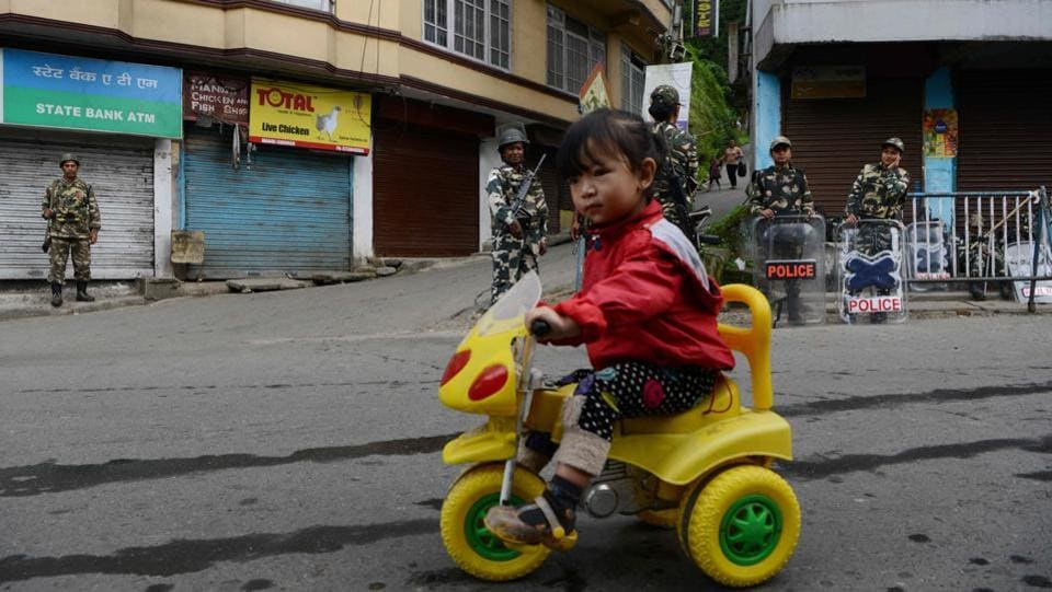 A child rides her tricycle as paramilitary personnel stand guard in the background in Darjeeling, on June 16, 2017. (Diptendu Dutta/AFP)