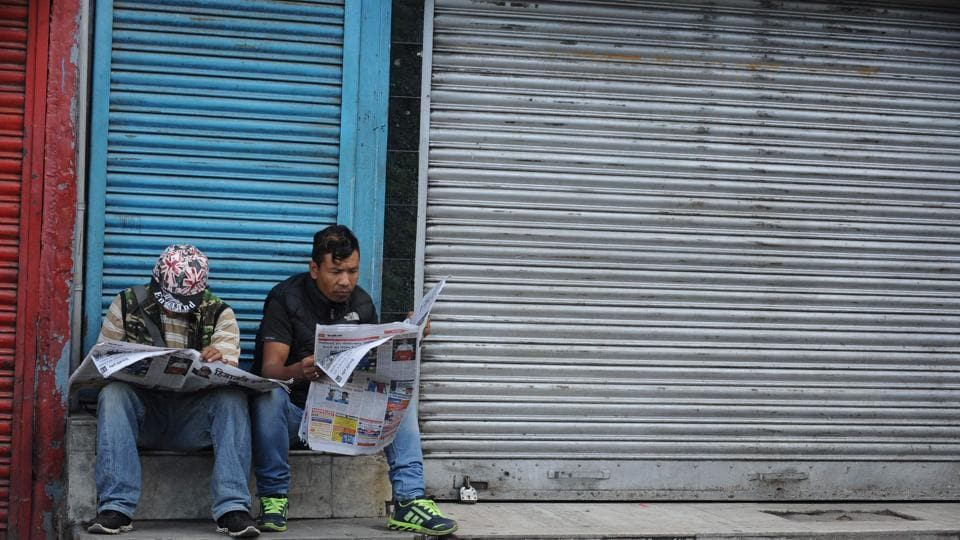 Resident sit outside a shuttered shop reading newspapers with normal life at a pause and an indefinite strike in place. (Diptendu Dutta/AFP)
