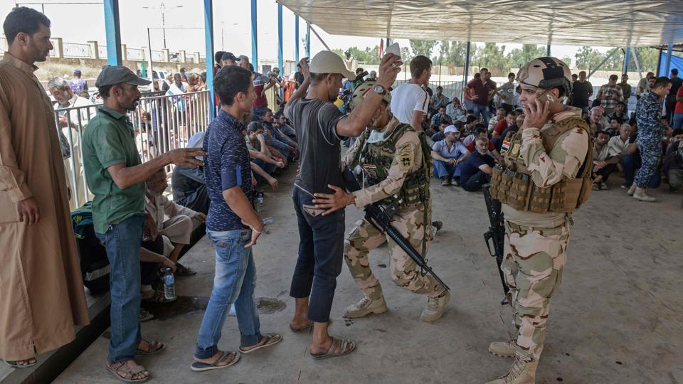 An Iraqi soldier frisks a displaced Iraqi man at a temporary camp in the compound of the closed Nineveh International Hotel in Mosul on June 16, 2017 which was recovered by Iraqi troops from Islamic State group fighters earlier in the year.  India said it was in touch with countries that could help it locate its missing citizens.