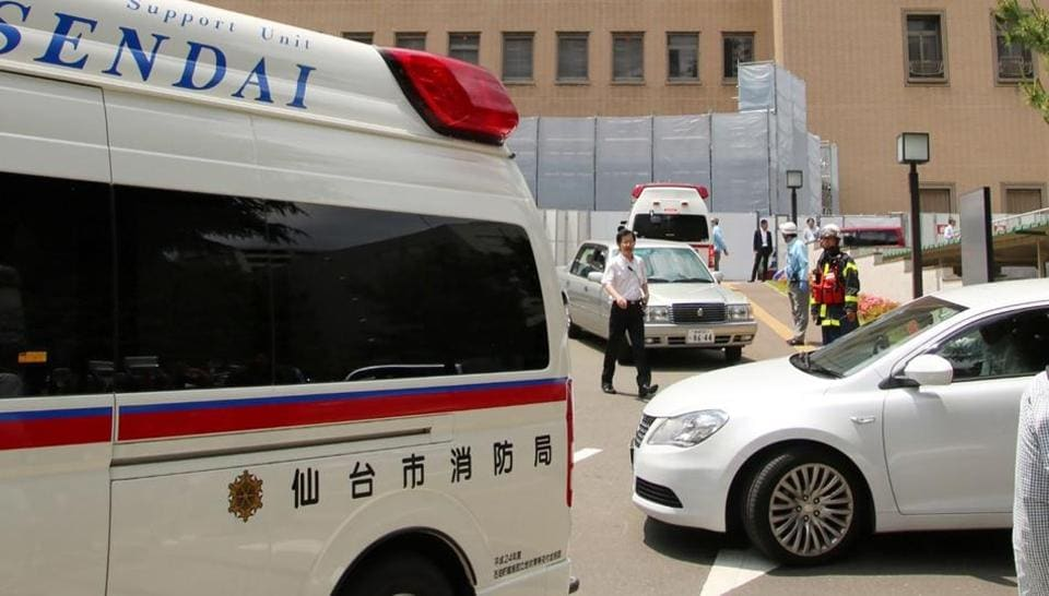 An ambulance and police cars at the Sendai district court where a man stabbed two court officers on Friday.
