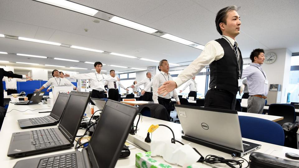 Employees of an information technology company exercising together in their office after lunchtime in Tokyo.  'Doing these exercises in the morning when you arrive at work or just after lunch when your head is not completely into working —let's you get ready and say 'OK let's do the job,'' said Adoc's Lay. (TORU YAMANAKA  / AFP)