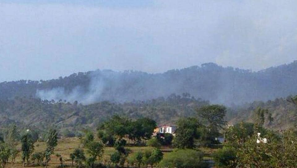 Smoke billows from the hills after shelling from Pakistan in Nowshera sector.