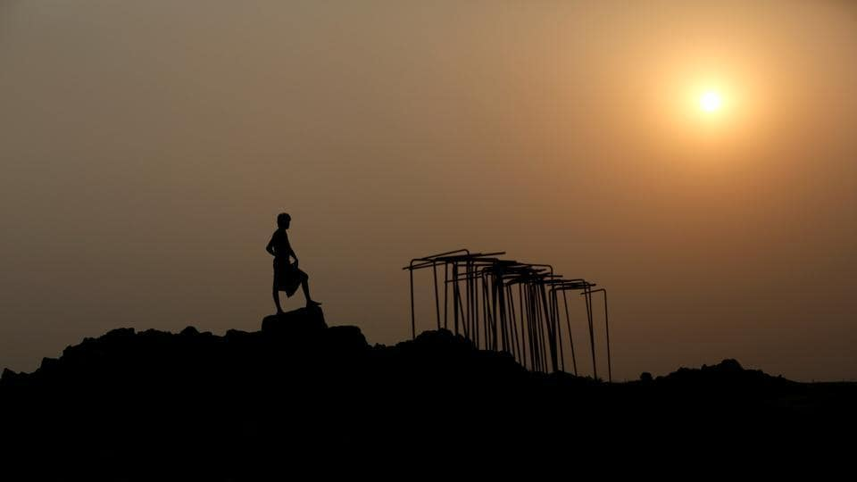 An Indian labourer is silhouetted as he works to build a bridge for the new railway in Nepal. (Navesh Chitrakar / REUTERS)