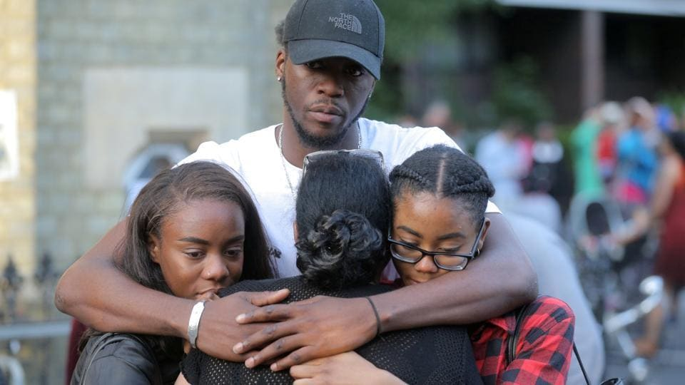 People comfort each other after a prayer vigil outside Notting Hill Methodist Church close to the tower block severely damaged by a serious fire, in north Kensington, West London, Britain June 15, 2017.