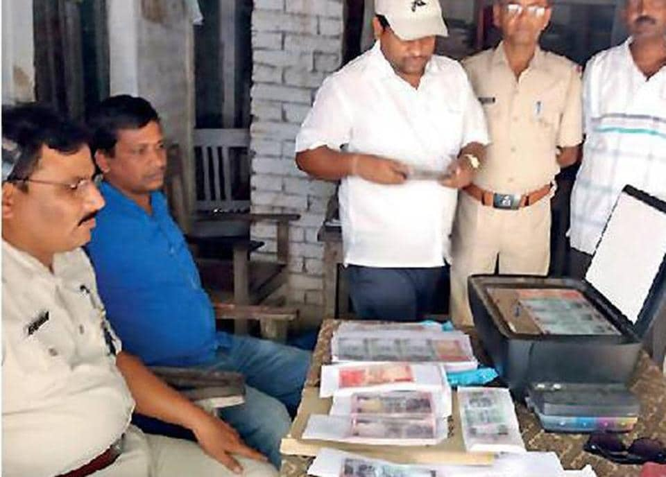 Police officials with recovered counterfeit notes at Hathaudi police station in Muzaffarpur district.