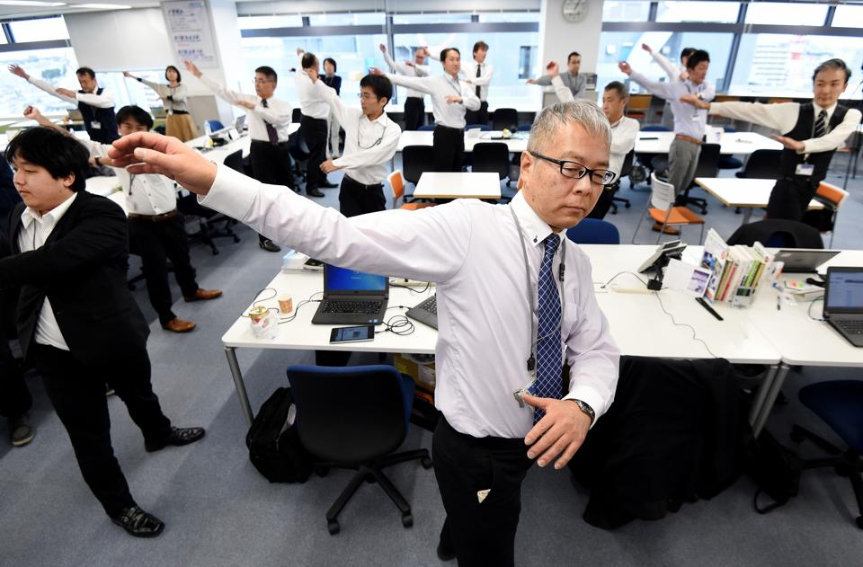 At the stroke of 1:00pm, a group of Tokyo IT workers spring from their desks for a few minutes of rigorous bending, stretching and thrusting as a voice on the radio instructs them — 'ichi, ni, san (one, two, three)'.  A growing number of Japanese companies are encouraging exercise breaks, in the hope of keeping employees limber and productive for longer, as the nation contends with a shrinking labour pool and one of the world's fastest ageing populations. (TORU YAMANAKA  / AFP)