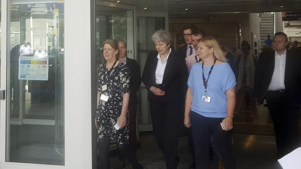 Britain's Prime Minister Theresa May, centre, leaves the Chelsea and Westminster Hospital in London after visiting people who were injured in the Grenfell Tower fire.