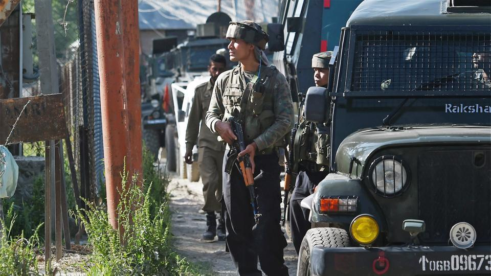 Army jawans stand guard during an encounter with militants at Arwani village of Anantnag district of south Kashmir on Friday.