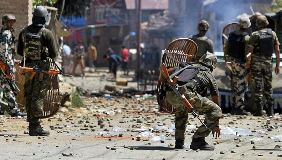 CRPF personnel face protesters throwing stones on them during a protest at Arwani village of Anantnag district of south Kashmir on Friday.