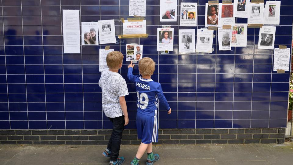 Two boys look posters of people missing in the Grenfell apartment tower block fire in North Kensington, London, Britain, June 17, 2017.
