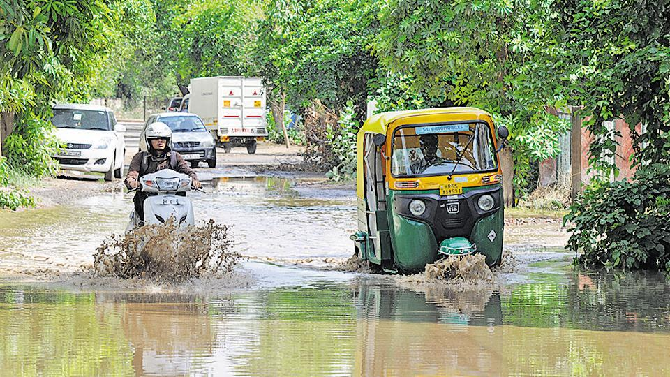 Motorists navigate a waterlogged road in Sushant Lok 1 on Friday.
