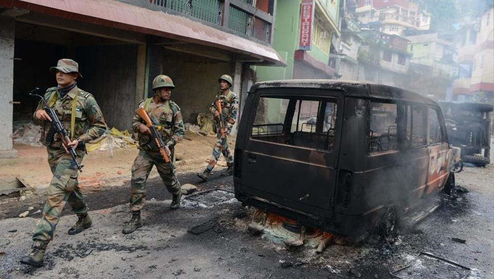 Soldiers patrol near burnt out vehicles after clashes with supporters of the separatist Gorkha Janmukti Morcha (GJM) group in Darjeeling on June 17, 2017.