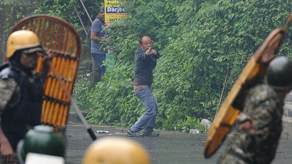 A supporter of the separatist Gorkha Janmukti Morcha fires a slingshot during clashes with security forces in Darjeeling on Saturday.