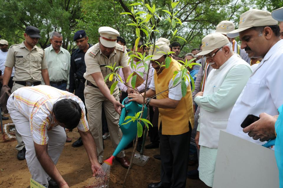 Union minister for environment Dr Harsh Vardhan (in jacket) plants a sapling in Bhondsi  village on Saturday.