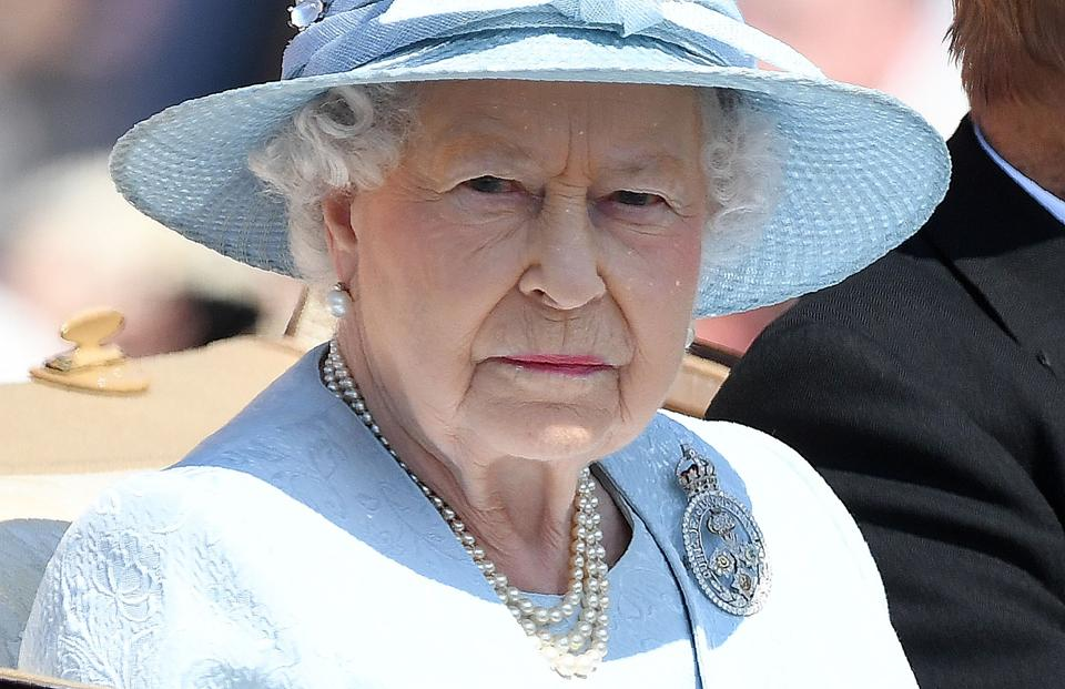 Queen Elizabeth II travels in a horse-drawn carriage on her way for the Queen's Birthday Parade.