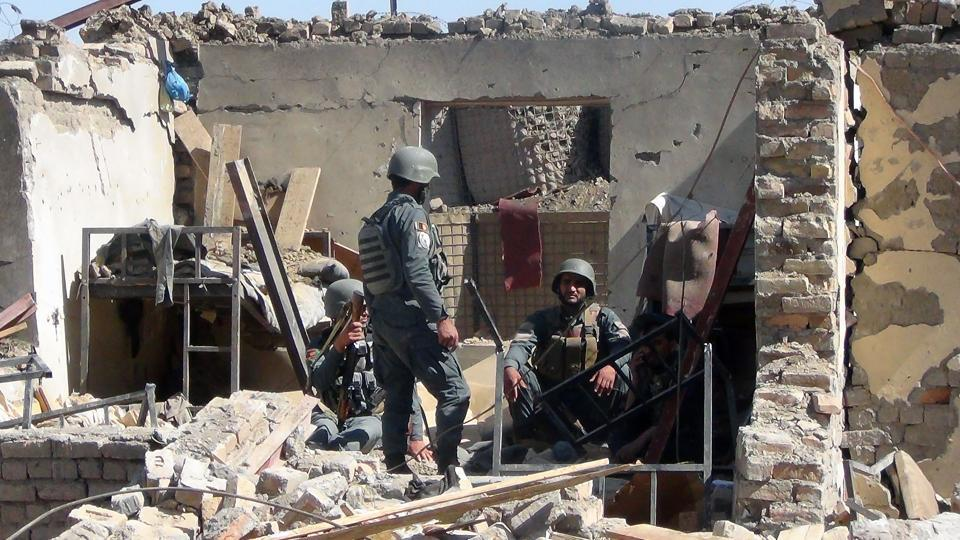 Afghan policemen gather at the site of a suicide bombing attack on the police headquarters in Gardez, capital of Paktia province.