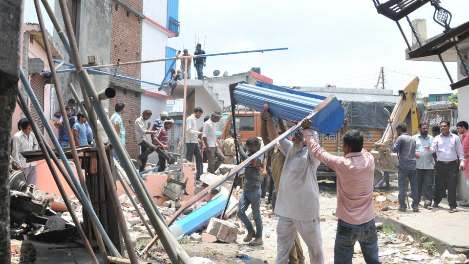 Traders remove scrap materials from site after anti-encroachment drive by MDDA at Transport Nagar in Dehradun.