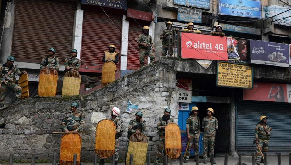 Indian police stand guard next to shuttered stores in Darjeeling on June 18, 2017, following a day of clashes with supporters of the separatist Gorkha Janmukti Morcha (GJM) group.