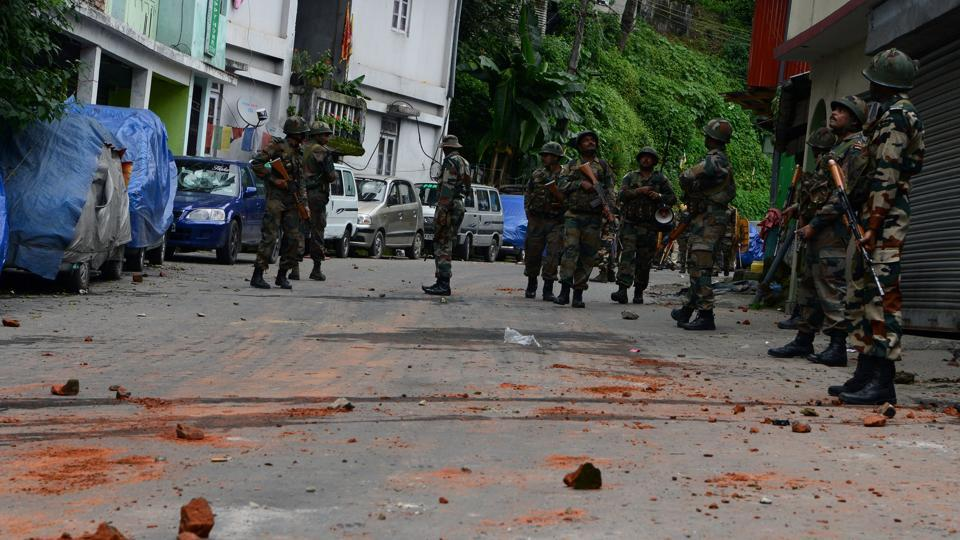 Soldiers patrol next to remains of bricks thrown by supporters of the Gorkha Janmukti Morcha (GJM) group after clashes in Darjeeling.