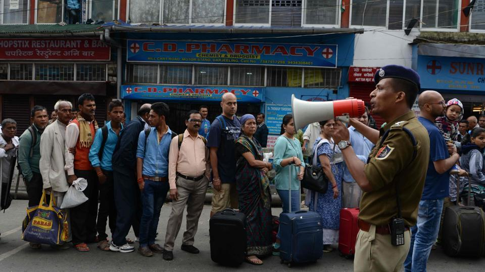 A policeman uses a megaphone to organise queues of tourists waiting to leave amid clashes between security personnel and protesters after the Gorkha Janmukti Morcha (GJM) called an indefinte strike in Darjeeling.
