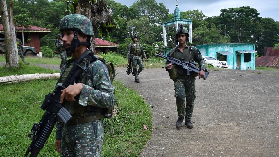 Philippine Marines patrol a walkway after engaging with Islamist militants in Marawi on the southern island of Mindanao on June 18, 2017. Philippine troops pounded Islamist militants holding parts of southern Marawi city with air strikes and artillery on June 17 as more soldiers were deployed and the death toll rose to more than 300 after nearly a month of fighting.
