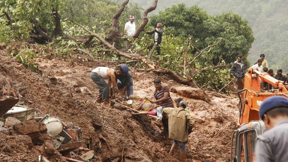 Rescue workers carry the body of a victim at the site of a landslide in Malin village, in Maharashtra on Wednesday. Torrential rains triggered a massive landslide that buried a remote village in western India.