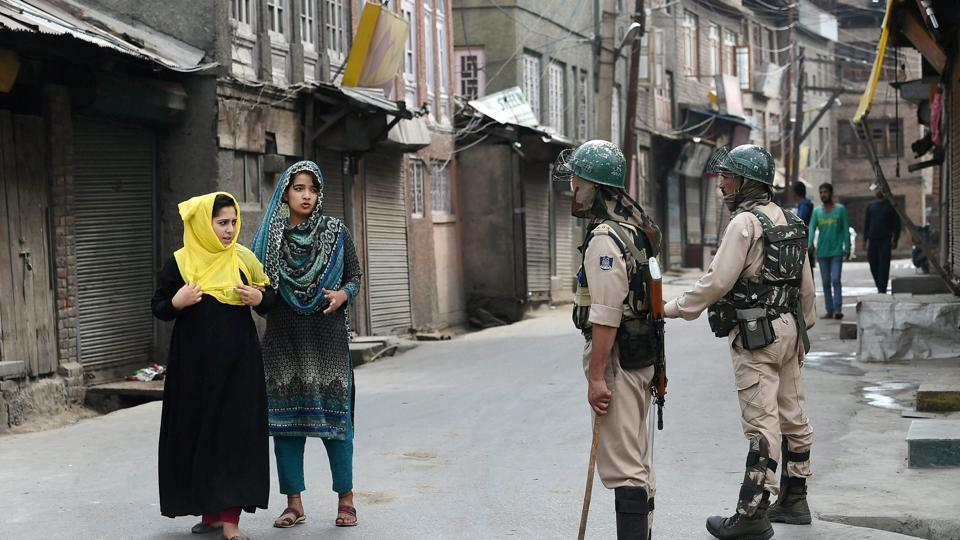 Girls seek permission from security personnel during restrictions imposed in the parts of the Valley following the killing of 2 civilian, in Srinagar on Friday.