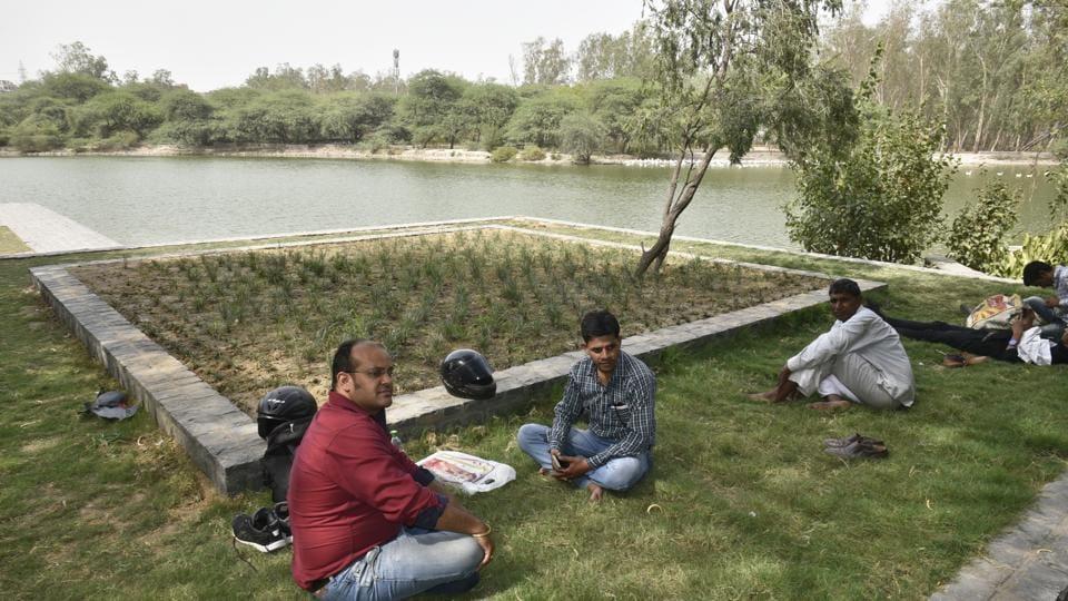 Delhi residents take rest at Sanjay Jheel in Mayur Vihar in New Delhi on Thursday.