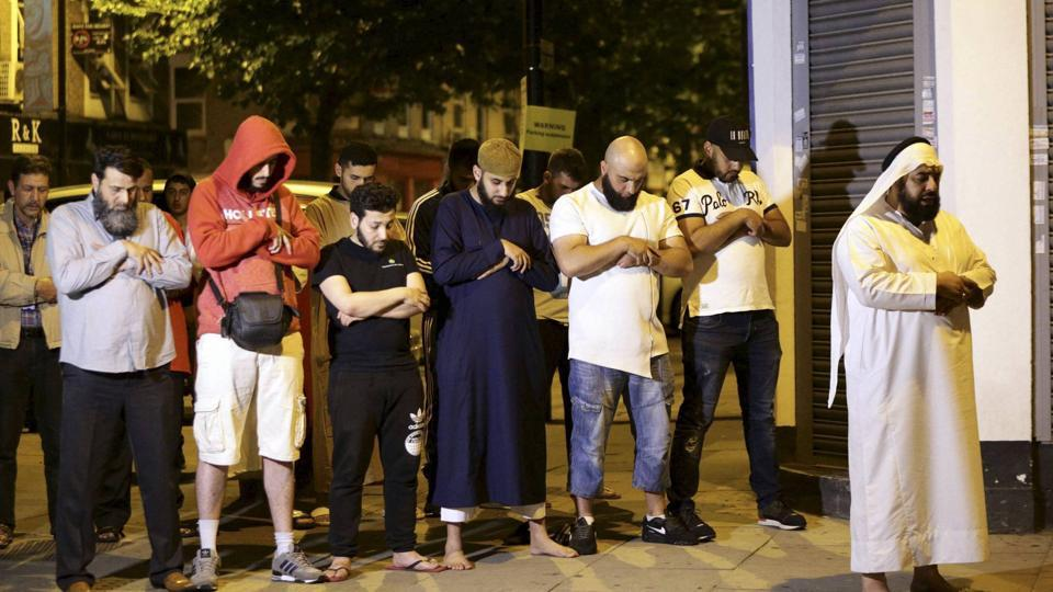 Local people observe prayers at Finsbury Park where a vehicle struck pedestrians in London Monday, June 19.