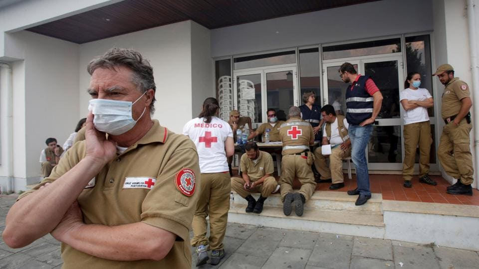 Red Cross and other relief personnel are seen outside a relief centre for people affected by the forest fire. (Miguel Vidal/REUTERS)