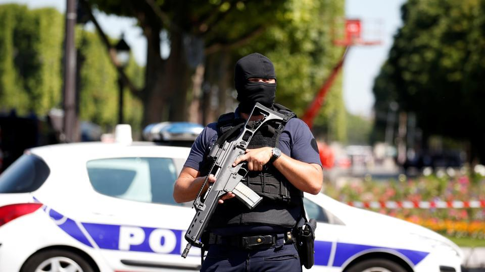 A masked French policeman secures the area on the Champs Elysees avenue.