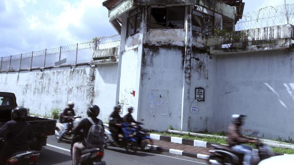 Bikers drive by a wall of Kerobokan prison from which four foreign inmates have escaped in Bali, Indonesia, Monday, June 19, 2017.