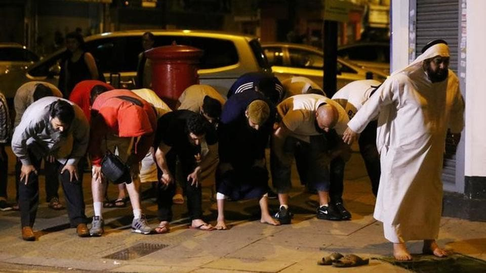 Men pray near the scene of the accident after a vehicle collided with pedestrians near the mosque. (REUTERS)