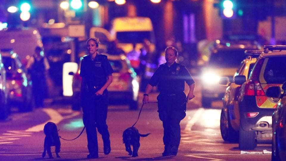 Police officers with sniffer dogs patrol the streets of North London. (REUTERS)