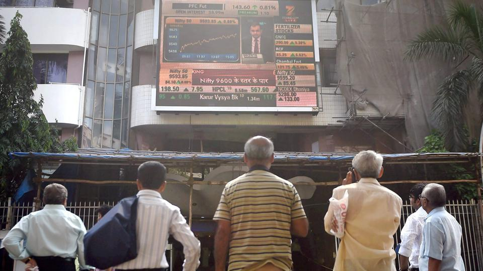 Investors watch the stock prices on a the display screen installed at Bombay Stock Exchange.