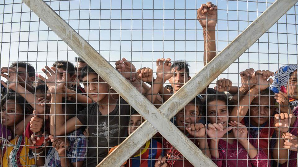 Displaced Iraqi children gather behind a fence at the Hasan Sham camp for internally displaced people. According to a new report by the United Nations High Commissioner for Refugees (UNHCR), a record 65.6 million people worldwide were forcibly displaced from their homes due to conflict or persecution by the end of 2016. The number marks a jump of 300,000 from the end of 2015. 'This equates to one person becoming displaced every three seconds - less than the time it takes to read this sentence' the United Nations report said. (AFP)